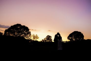 Silhouette of bride and groom, kissing at sunset at Arran Farm, Easley, SC